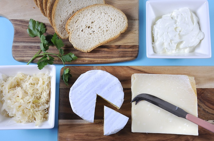 Healthy Food Diet: Probiotic Food including sour dough bread, sauerkraut, yogurt, Parmigiano-Reggiano and Camembert cheeses on wood chopping boards against a blue background.